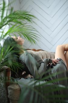 エレガントなドレスが付いているソファーで横になっているセクシーな女性