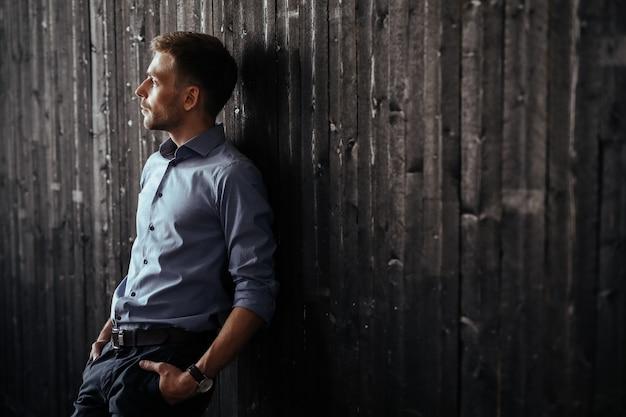 Молодой красивый бизнесмен позирует в помещении