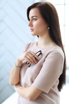 Красивая деловая женщина позирует в интерьер офиса