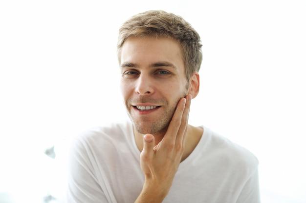 Человек, касаясь его борода, готов для бритья.
