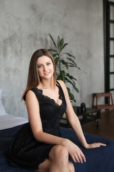 ソファーでポーズをとって若い魅力的な女性