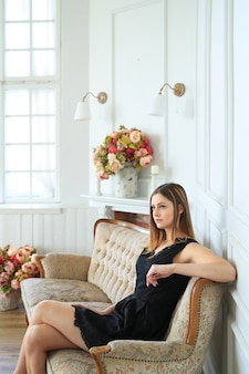 Молодая привлекательная женщина позирует на диване