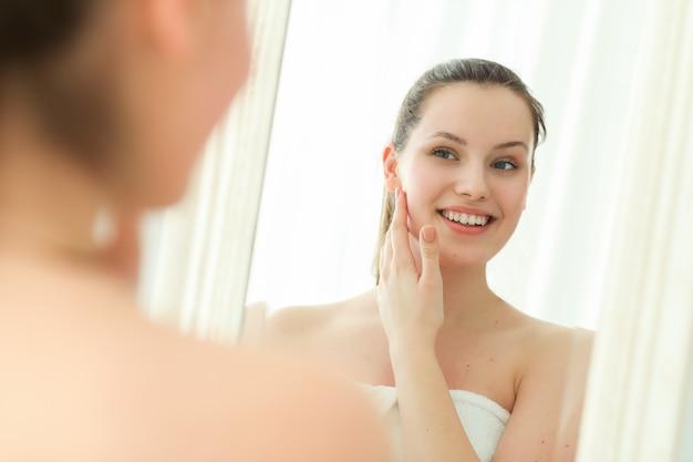 鏡で見ているシャワー後の体にタオルを持つ女性