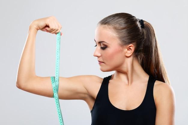 若い女性は彼女の腕を測定