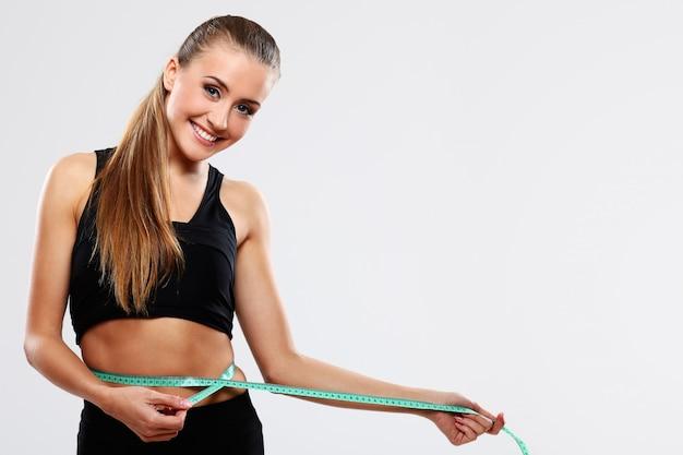 若い女性は彼女の腰を測定