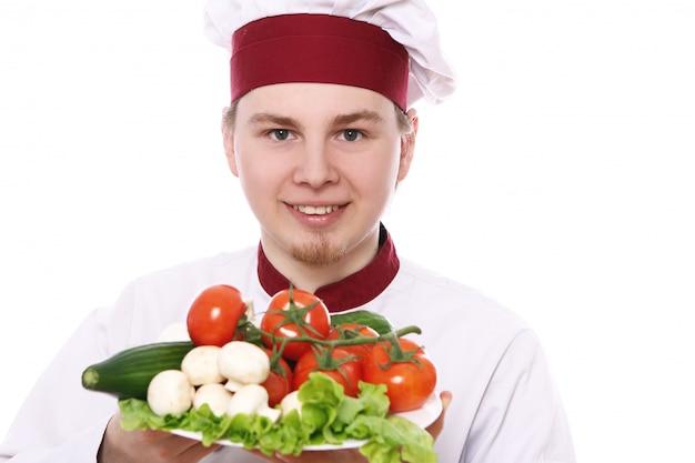 Молодой шеф-повар держит тарелку с овощами