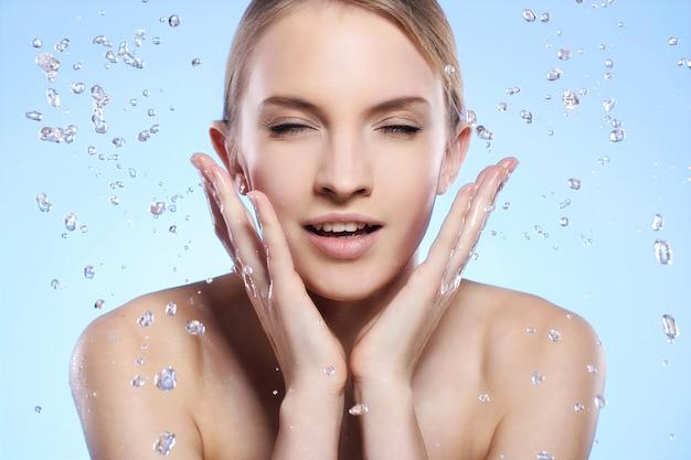 美しい女性が彼女の顔を洗う