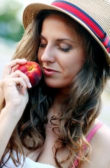 Молодая женщина со свежим персиком в руке