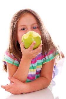 Милая девушка ест яблоко