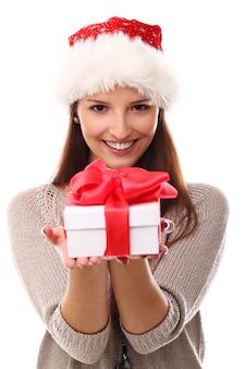 Портрет молодой женщины в новогодней шапке и подарочной коробке
