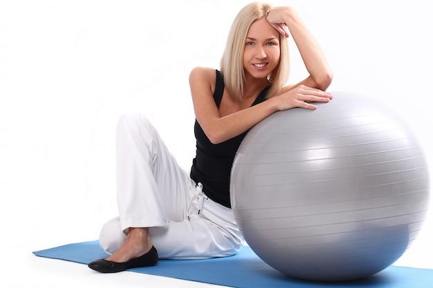フィットネスボールを持つ若い女