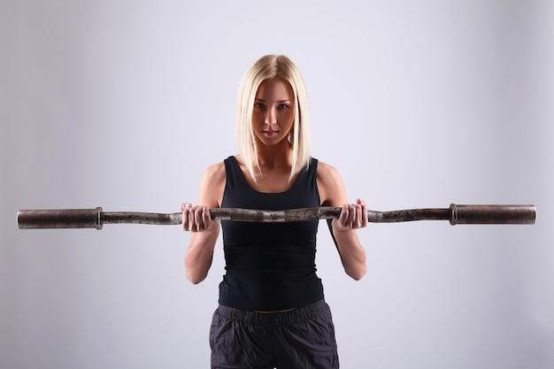 Молодая женщина спортсмена с штангой тренировки