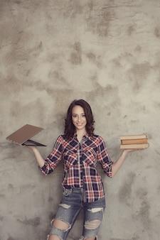 本とラップトップでポーズ美しい若い女性
