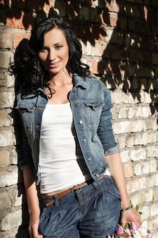 レンガの壁で美しい若い女性