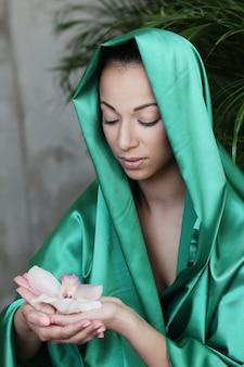 Красивая женщина с традиционным индийским костюмом и цветком на руках