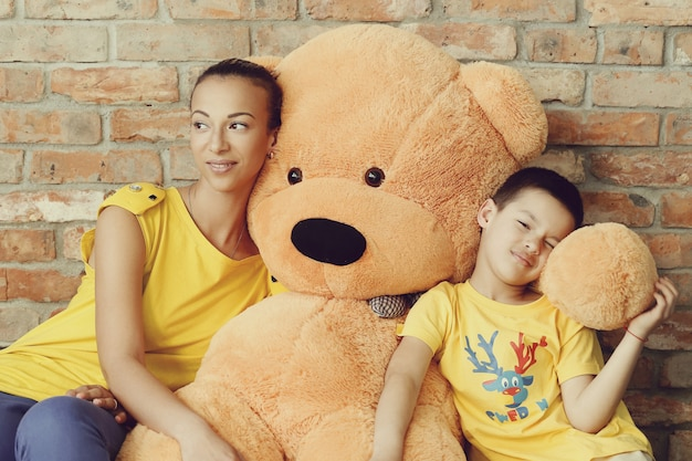 巨大なテディベアを持つ母と息子