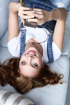ソファ、インテリアリビングルームで休んで素敵な若い女性