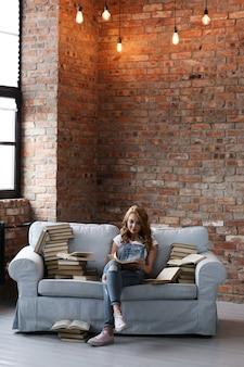 Молодая женщина отдыхает на диване с большим количеством книг