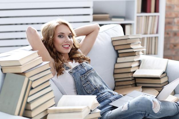 Молодая женщина отдыхает на диване с ноутбуком и много книг