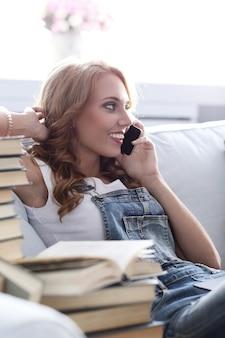 電話で話しているソファで休む若い女性