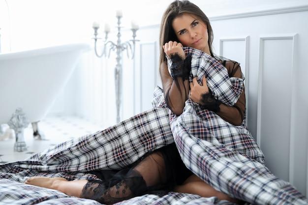 毛布が付いているベッドの上の黒のランジェリーの女性