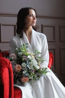 Невеста в свадебном платье сидит на красной скамейке