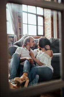 ソファーに座って会話するカップル