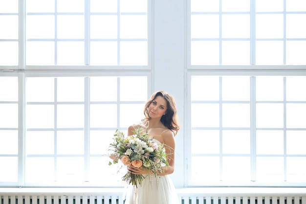 花の花束を保持している白いドレスの花嫁
