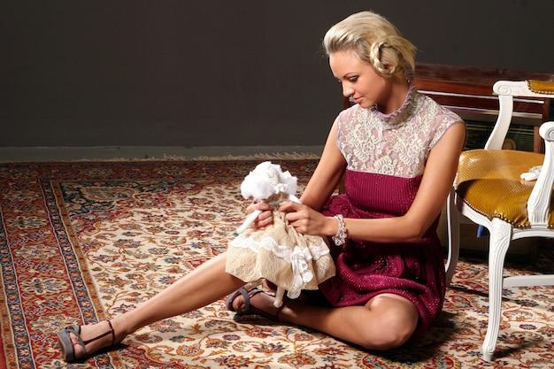 ピンクの人形のファッション衣装の金髪モデル