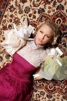 床に横になっているチュールのディテールが付いたピンクのドレスのブロンドモデル