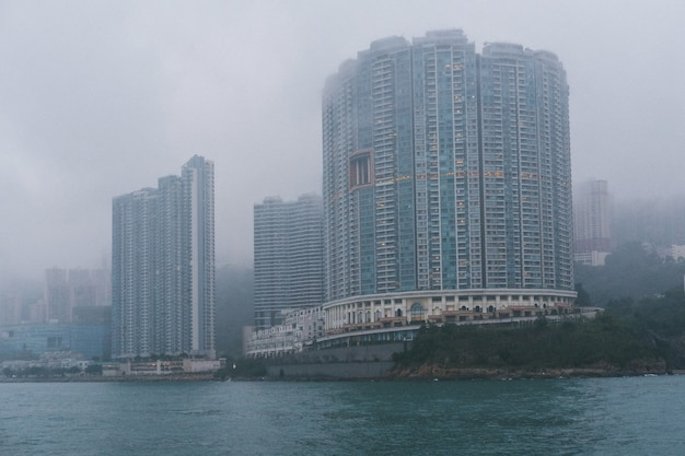 Серые бетонные высокие небоскребы на побережье в туманную погоду