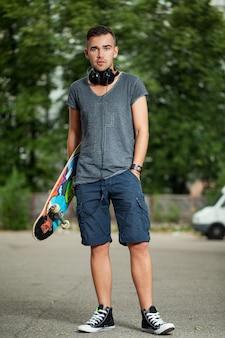 Красивый парень с наушниками и скейтбордом