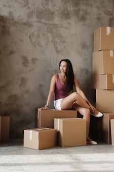 Молодая женщина переезжает на свою новую квартиру