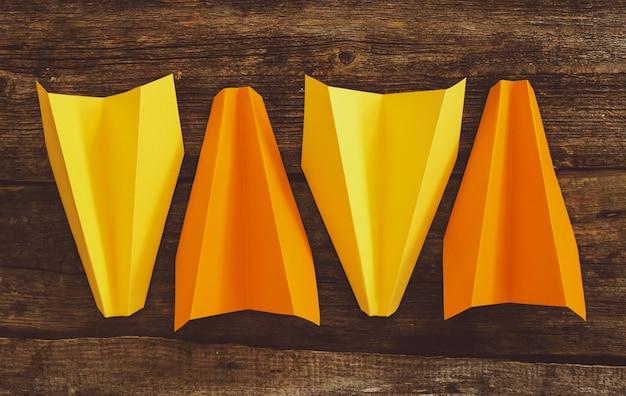 木製のテーブルの上の紙飛行機。旅行のコンセプト