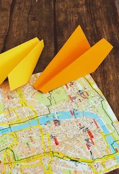 マップ上の紙飛行機。旅行のコンセプト