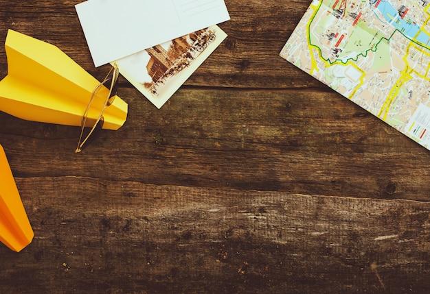 木製のテーブルの地図と紙飛行機。旅行の概念の背景