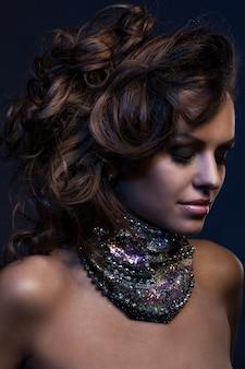 大きなネックレスを持つ美しい女性