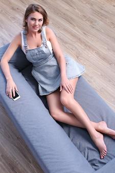 Красивая взрослая женщина, лежа на диване