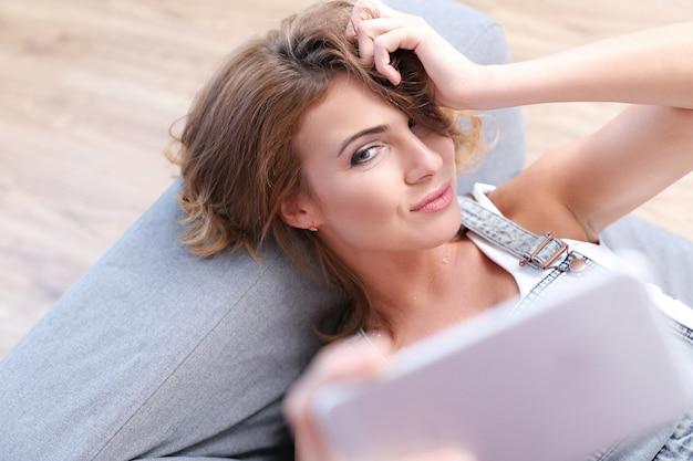 Красивая взрослая женщина, принимая селфи в диване