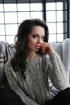 Привлекательная брюнетка женщина позирует на диване
