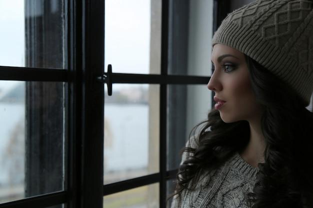 Привлекательная женщина смотрит в окно