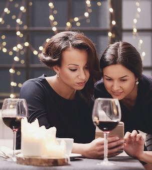 レストランでスマートフォンを見ている女性
