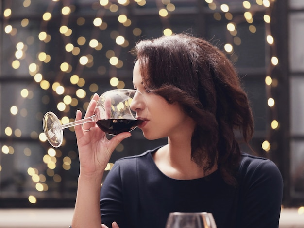 Женщина в ресторане пьет бокал