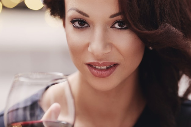 Женщина в ресторане держит бокал