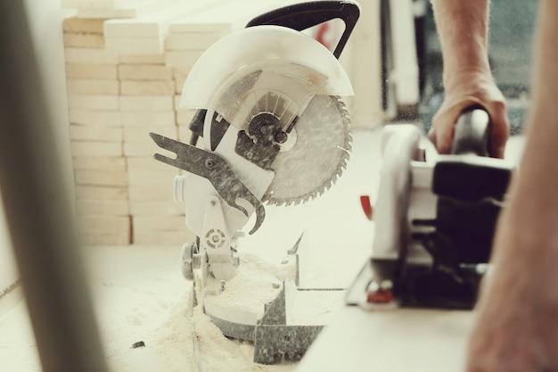 Человек с помощью электрической пилы в столярной мастерской