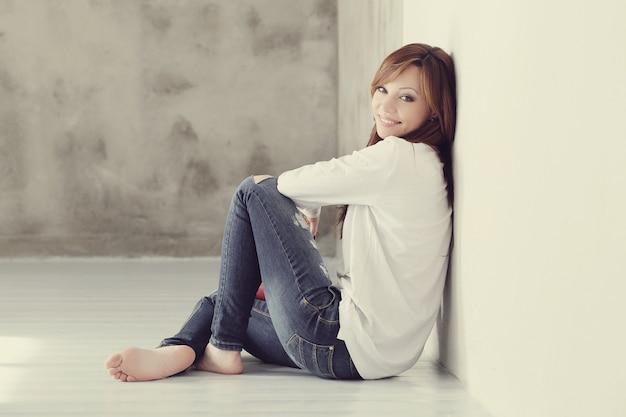 床に座って素敵で魅力的な大人の女性