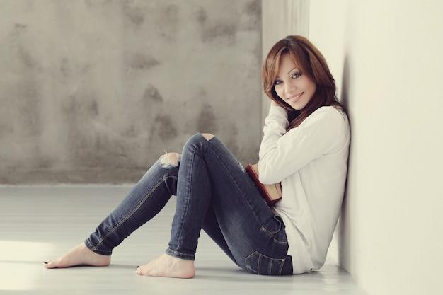 Прекрасная и очаровательная взрослая женщина сидит на полу