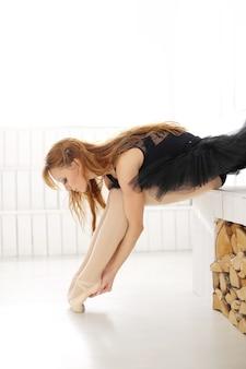 黒い白鳥のために練習して黒いドレスの古典的なバレリーナの女性