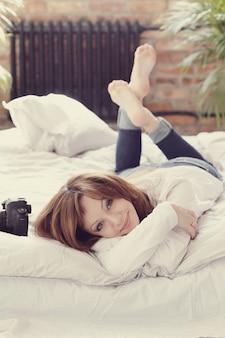 写真カメラでベッドに横たわっている写真家女性