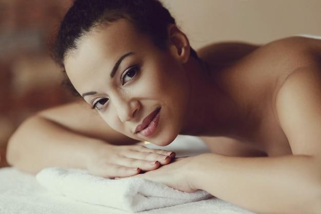 スパでリラックスできるマッサージを受けるアフリカ系アメリカ人の女性